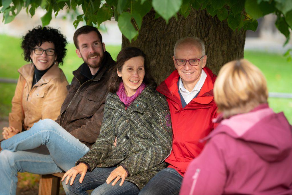 Thomas Semmelmann engagiert sich für seine Region und unterhält sich hier mit drei Frauen und zwei Männern sitzend auf einer Bank unter einem Baum