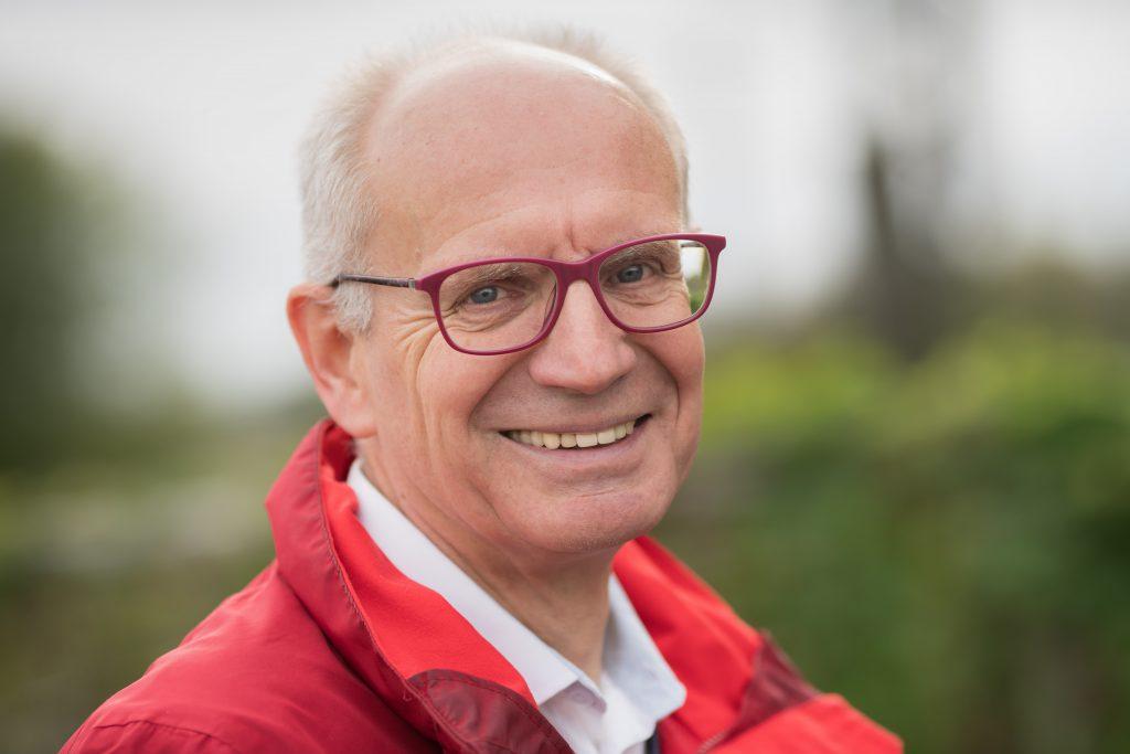 Thomas Semmelmann trägt eine rote Brille sowie eine rote Jacke und lächelt in die Kamera