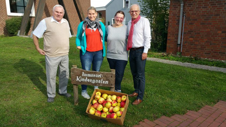 Auf der Rasenfläche der Kita Immanuel mit zwei Mitarbeiterinnen und einem Genossen bei der Übergabe von Äpfeln
