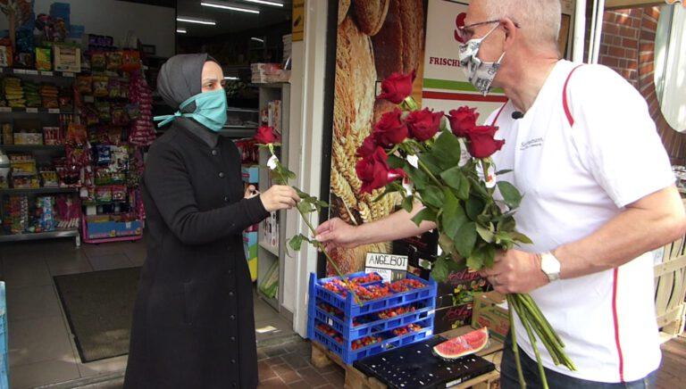 Thomas Semmelmann übergibt rote Rosen an eine Frau
